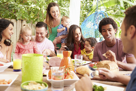 3 6 months: Group Of Families Enjoying Outdoor Meal At Home