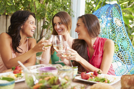 Three Female Friends Enjoying Meal Outdoors At Home photo