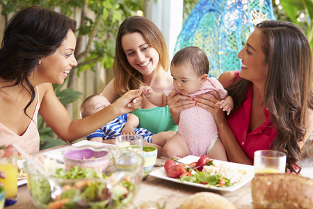 Group Of Mothers With Babies Enjoying Outdoor Meal At Home photo