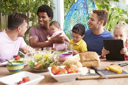 Group Of Fathers With Children Enjoying Outdoor Meal At Home photo
