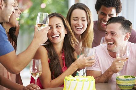 tomando alcohol: Grupo de amigos celebrando cumplea�os en casa Foto de archivo