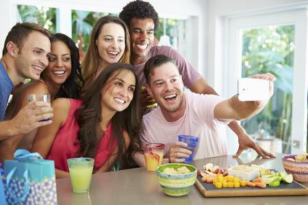 hombre comiendo: Grupo de amigos que toman Autofoto Si bien Celebrando Cumpleaños