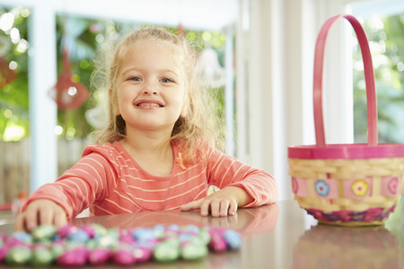Girl With Chocolate Easter Eggs And Basket At Home