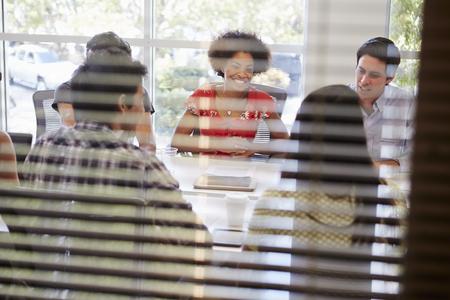 multi cultural: Designers Having Meeting Viewed Through Window