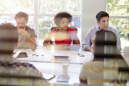 collaborating: Designers Having Meeting Viewed Through Window
