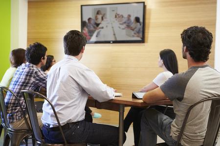 mujer viendo tv: Diseñadores sentado en la mesa de reuniones En Mirando a la pantalla