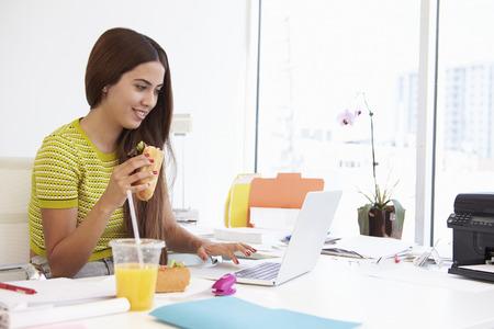 Mujer Que Trabaja En Design Studio que almuerzan en el Escritorio