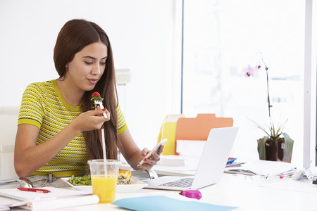 Woman Working In Design Studio Having Lunch At Desk Stock Photo