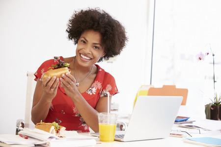 lunch: Mujer Que Trabaja En Design Studio que almuerzan en el Escritorio