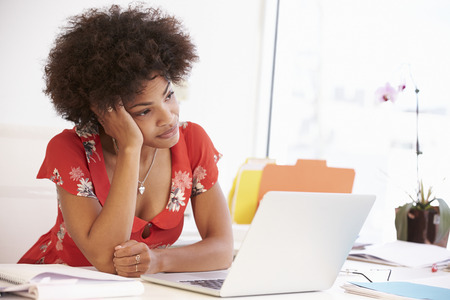 ležérní: Frustrovaný žena pracující u stolu v Design Studio Reklamní fotografie