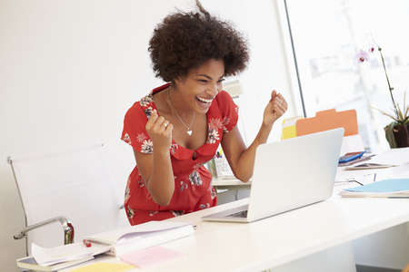 Excited Woman Working At Desk In Design Studio photo