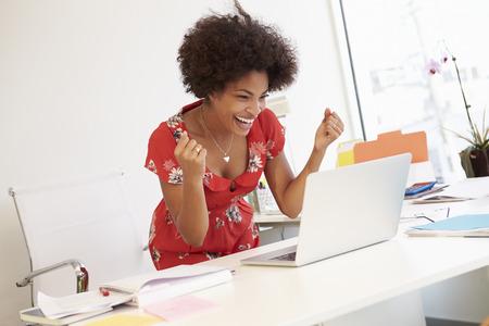Opgewonden vrouw werken bij bureau in Design Studio
