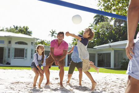 female volleyball: Family Playing Volleyball In Garden At Home