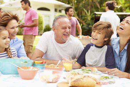 fiesta familiar: Multi generacional disfruta de la comida en jard�n junto