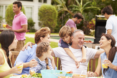 Multi Generation Family Enjoying Meal In Garden Together photo