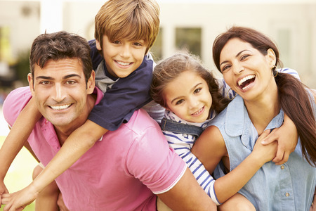 famille: Portrait Of Happy Family Dans jardin à la maison
