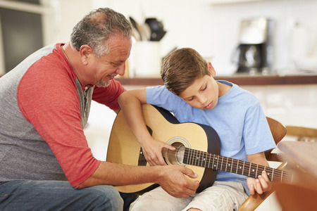 boy playing guitar: Grandfather Teaching Grandson To Play Guitar