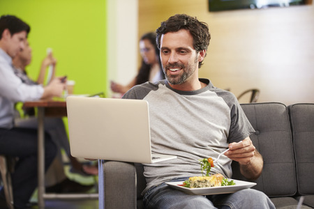 work break: Man Sitting On Sofa And Eating Lunch In Design Studio