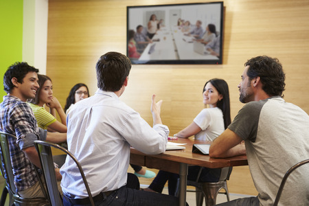 man watching tv: Designers Sitting Around Table In Meeting Looking At Screen