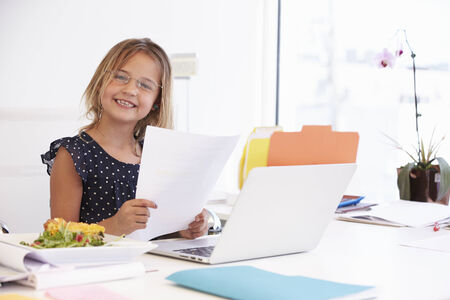 Girl Pretending To Be Businesswoman Working At Desk photo