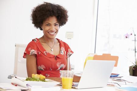 women black: Mujer Que Trabaja En Design Studio que almuerzan en el Escritorio