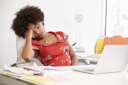 sleeping at desk: Tired Woman Working At Desk In Design Studio Stock Photo
