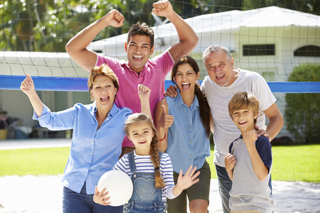 active: Multi Generation Family Playing Volleyball In Garden