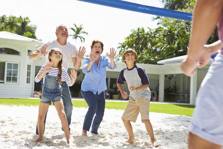 grandchildren: Grandparents And Grandchildren Playing Volleyball In Garden