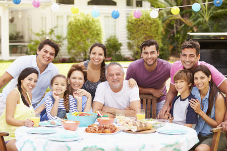 Multi Generation Family Enjoying Meal In Garden Together Imagens