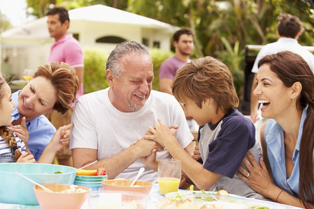 Multi Generation Family Enjoying Meal In Garden Together Stock Photo - 33549409