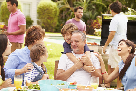 Multi Generation Family Enjoying Meal In Garden Together Stockfoto