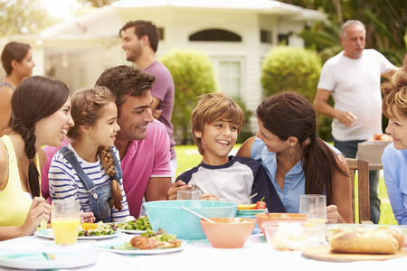 Multi Generation Family Enjoying Meal In Garden Together Stockfoto