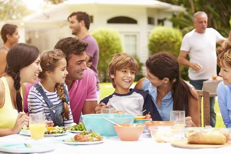Multi Generation Family Enjoying Meal In Garden Together Standard-Bild