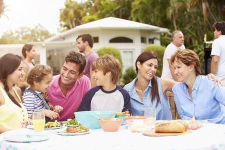 Multi Generationen Familie, die Mahlzeit genießen zusammen im Garten Standard-Bild