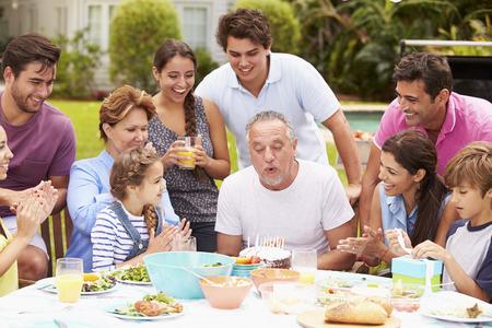 Multi Generation Family Celebrating Birthday In Garden photo