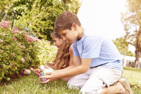 庭でイースターエッグ ハントを持つ 2 人の子供