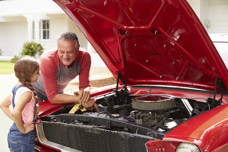 Grandfather And Granddaughter Work On Restored Classic Car Stock Photo