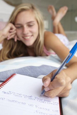Teenage girl writing in diary Stock Photo