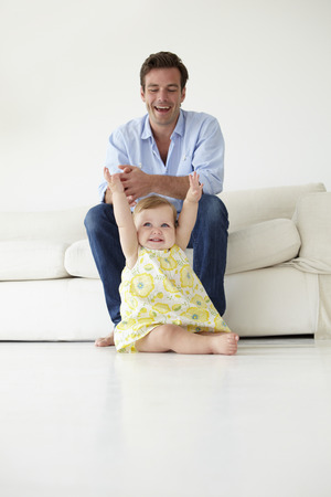 adoring: Doting father with baby daughter at home