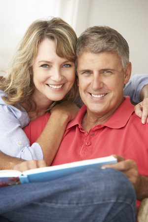 attractive female: Mid age couple reading book together