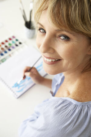 mid age: Mid age woman painting with watercolors Stock Photo
