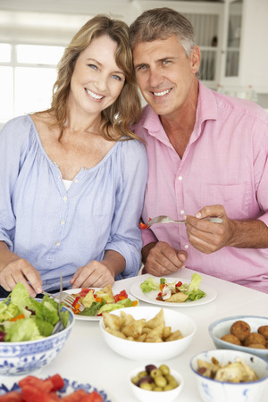 Mid age couple enjoying meal at home