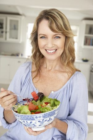 mid age: Mid age woman eating salad