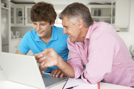 mid teens: Father and teenage son using laptop