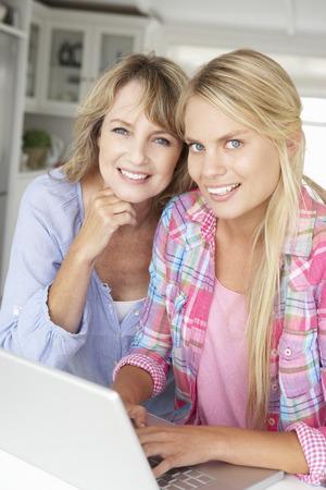 madre e hija adolescente: Madre e hija adolescente utilizando el portátil Foto de archivo