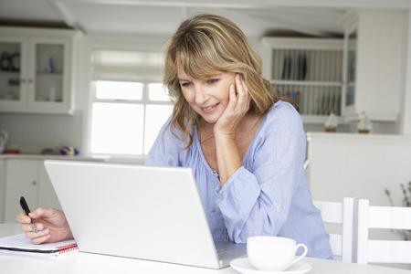 pensando: Mulher meados de da idade trabalhando em casa no laptop Banco de Imagens