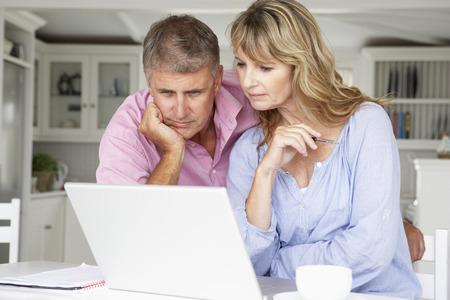 lectura y escritura: Mediados de pares de la edad que trabajan en casa en la computadora port�til Foto de archivo