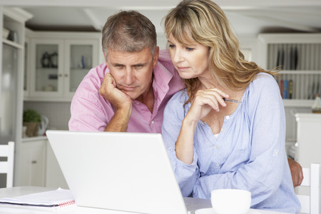Mid age couple working at home on laptop Imagens