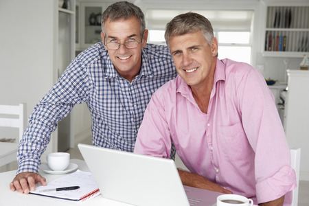 Mid age men working on laptop at home photo