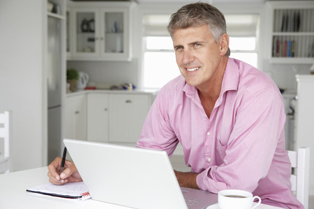 mid age: Mid age man working on laptop at home